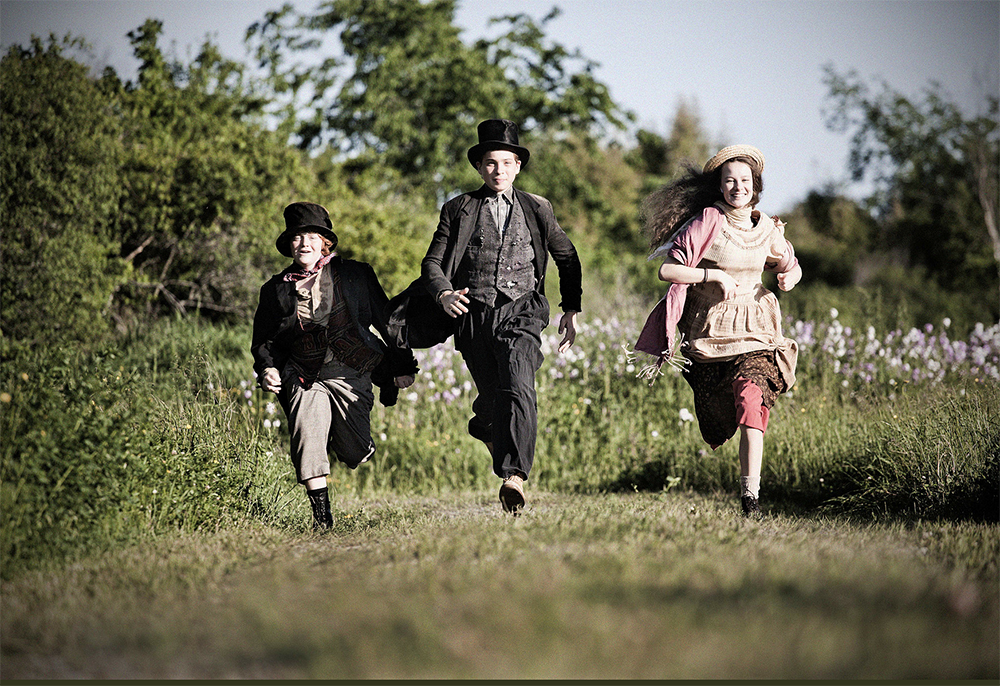 Three children running through a field in costume.