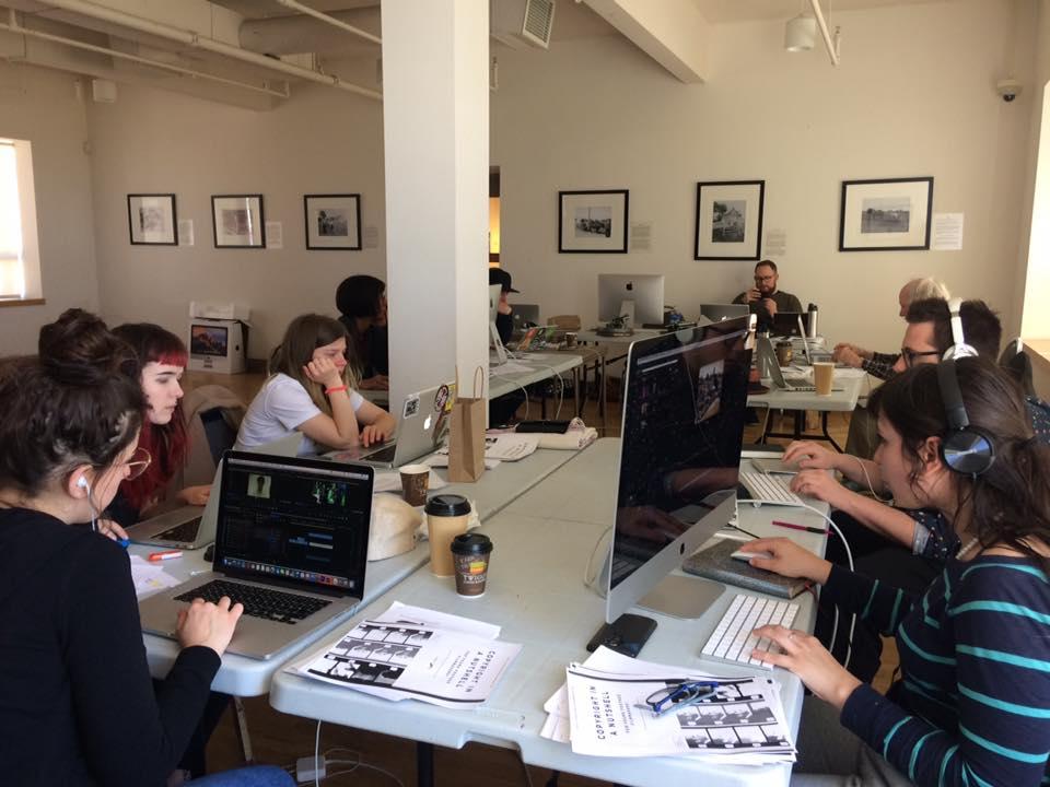 Des jeunes qui participent au programme sont assis autour de tables et travaillent sur des ordinateurs.