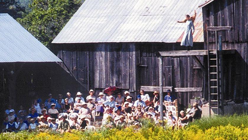 Assis à l'extérieur, l'auditoire lève les yeux pour regarder un acteur qui joue sur une scène surélevée à côté d'une grange.