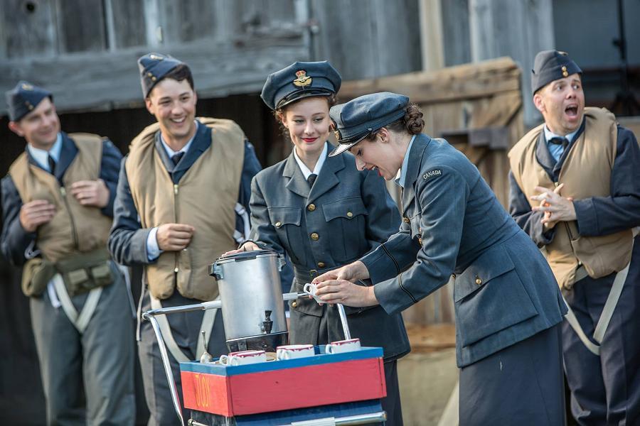 Des acteurs et des actrices en uniforme de l'Aviation royale canadienne à l'époque de la Seconde Guerre mondiale plaisantent près d'un chariot à café dans la pièce Bombers: Reaping the Whirlwind, produite par 4th Line Theatre.