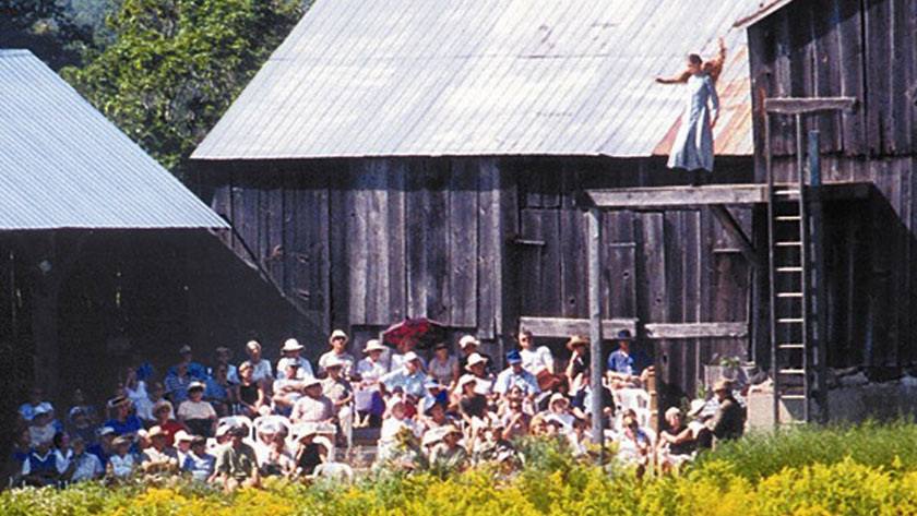 A seated audience looks up as an actor performs on a raised stage next to a barn.