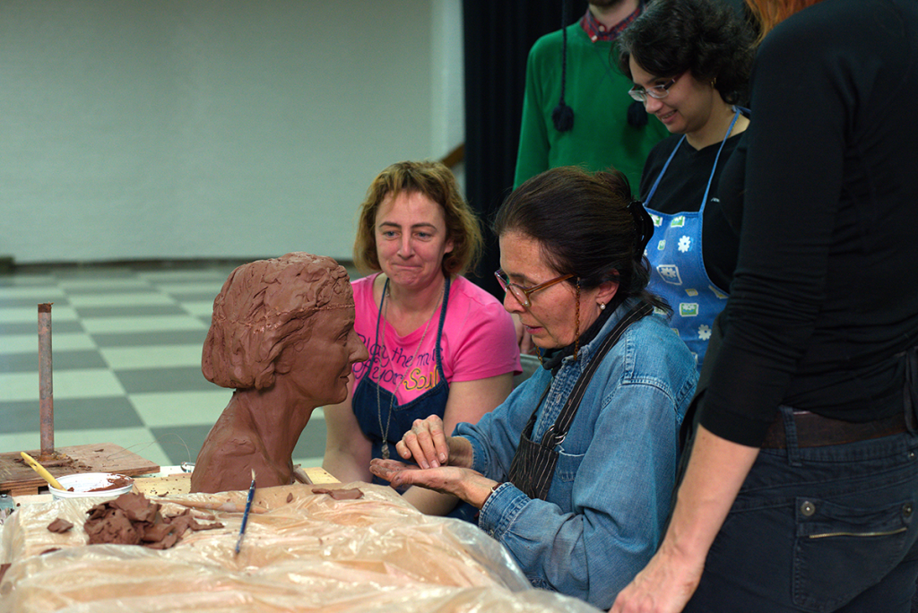 A woman sits working on a sculpture of a bust while a group of people watch.