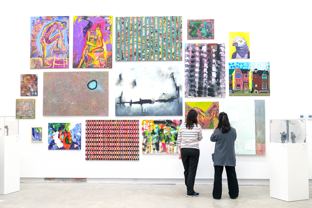 Two people stand facing a wall of full of hanging visual artworks in a gallery.