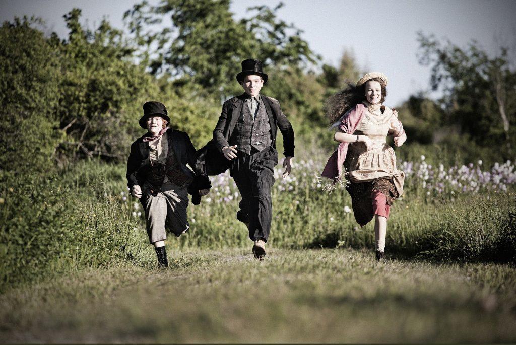 Trois enfants en costume courent à travers un champ.