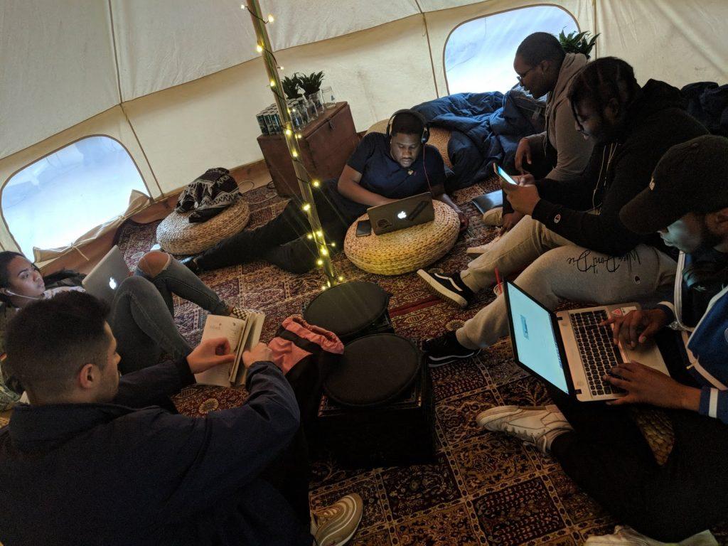 Assis par terre, les participants au projet Remix travaillent sur des ordinateurs portatifs.