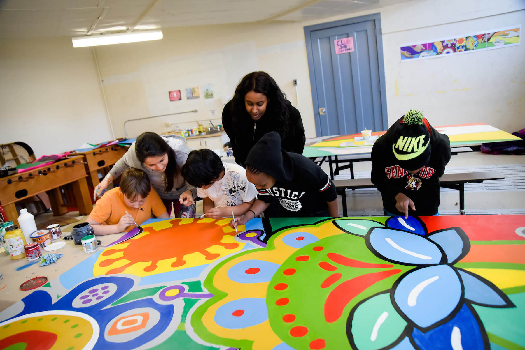 Community-engaged artist Claudia Salguero (background left) works on a mural with participants of MASC's Awesome Arts program in Ottawa. (Photo: Micheline Shoebridge)